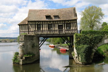 Raised Normandy half-timbre house over water, seen on Normandy vacation packages tour