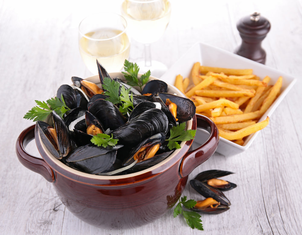 bowl of mussels and french fries in Normandy vacations packages tours
